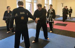 Black belt candidate performing joint locking techniques (Ki Bohn Soo)