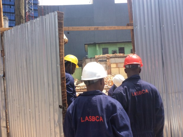 Men of the Lagos State Building Control Agency demolishing an illegal fencing on Sunday, September 18.