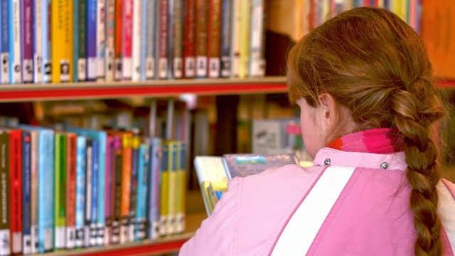 Girl looking at books in library_2057504072497870-159532