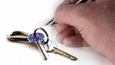 House keys and hand with pen