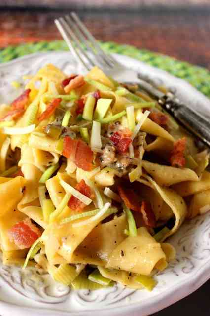 Pappardelle pasta with sauteed leeks and bacon.