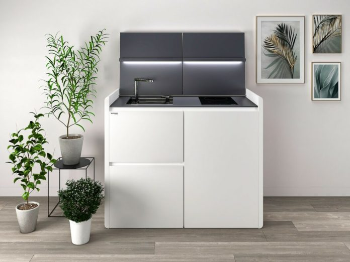 """With a width of 127 cm, height of 106 cm and depth of 63.7 cm, the """"K6"""" model from Kitchoo accommodates all the necessary kitchen functions in the smallest of spaces. Clever: the integrated LED lighting with storage for smartphone or cookbook in the flap. (Photo: Kitchoo)"""