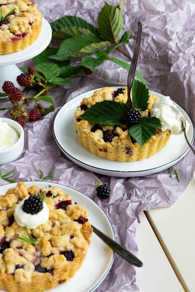 Kleine Brombeer-Streusel-Kuchen mit Rosmarin. Die kleinen Kuchen sind super schnell gemacht und schmecken mit frischen oder tiefgefrorenen Beeren. Ein Genuss für alle, die Beeren lieben. Passt zu jeder Kaffeetafel. Küchentraum & Purzelbaum | #backen | #brombeeren | #streusel