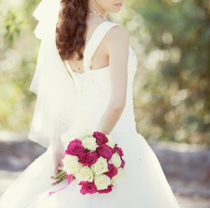 pink and white wedding bouquet of roses in the hands of the brid