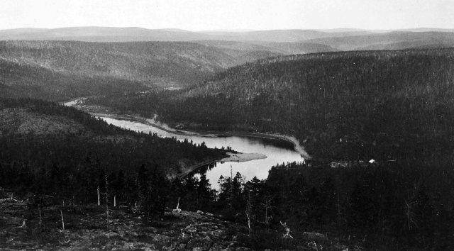Ivalojoki Palsitunturin laelta Ivalojoelle. OIkealla keskellä näkyy Ritakosken alapuolella sijainnut sahalaitoksen katto. Kuva geologi Erkki Mikkolan 1920-luvun lopulta. Hipputeoksen arkisto.