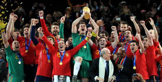 Spain's goalkeeper Iker Casillas (C) raises the trophy handed to him by FIFA President Sepp Blatter (4thR) and South Africa's President Jacob Zuma (3rdR) as Spain's national football team players celebrate winning the 2010 World Cup football final Netherlands vs. Spain on July 11, 2010 at Soccer City stadium in Soweto, suburban Johannesburg. NO PUSH TO MOBILE / MOBILE USE SOLELY WITHIN EDITORIAL ARTICLE - TOPSHOTS AFP PHOTO / GABRIEL BOUYS