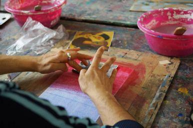 Hände, die einen Zeitungsausschnitt auf Acrylfare aufbringen.