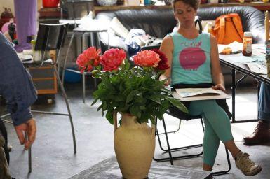Vase mit Blumenstrauß, auf einem Tisch stehend, und Teilnehmerin beim Abzeichnen des Stilllebens.