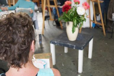 Blumenvase mit Strauß, steht auf Tisch und ist bereit zum Gemaltwerden.