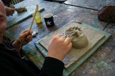 Hände beim Arbeiten mit Ton