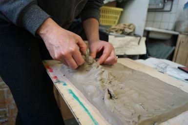 Zwei Hände, die aus flachem Rechteck aus Ton etwas Dreidimensionales formen.
