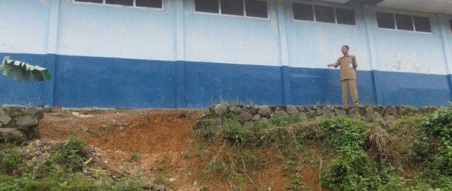 Muhammad Madnur, Kepsek SDN Bojong, Sukajaya, menunjukkan lokasi longsor di sekolahnya (dok. KM)
