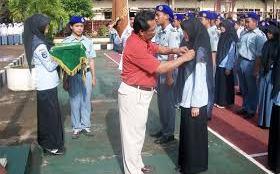 Wawan Gunawan, Kepala sekolah di SMK Bina Nusantara Cilaku, Cianjur, sedang menyematkan pin pada salah satu siswa nya. (dok. KM)