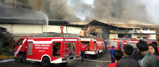Pemadam kebakaran berusaha memadamkan api yang tengah melalap gudang milik pabrik garmen di Cicurug, Sukabumi pada Selasa pagi 19/7 (dok. KM)