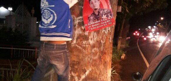 Warga mencabut spanduk kampanye Bakal Calon Bupati Bogor di Jalan Raya Puncak (dok. KM)
