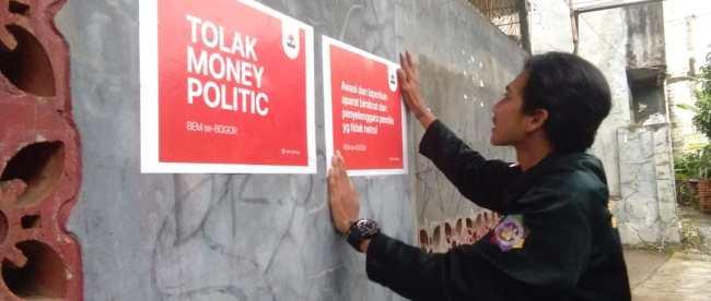 Seorang aktivis BEM Se-Bogor memasang stiker tolak money politics, Selasa 16/4/2019 (dok. KM)
