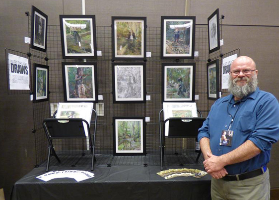 Kurt Brugel at illuxcon 2016 with women of the woods colored pencil drawings