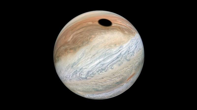 De schaduw van de maan Io valt op Jupiter
