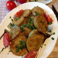 Pecen patlidzan koji je pohovan na tanjiru sa viljuskom i paradajzom