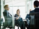 Female business executive listening to presentation by colleagues in office conference room