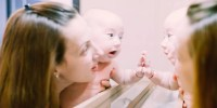 baby smiling in mirror