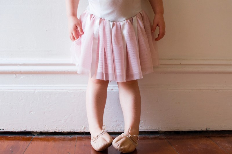 Toddler in pink tutu and ballet shoes standing in vintage hallway (cropped)
