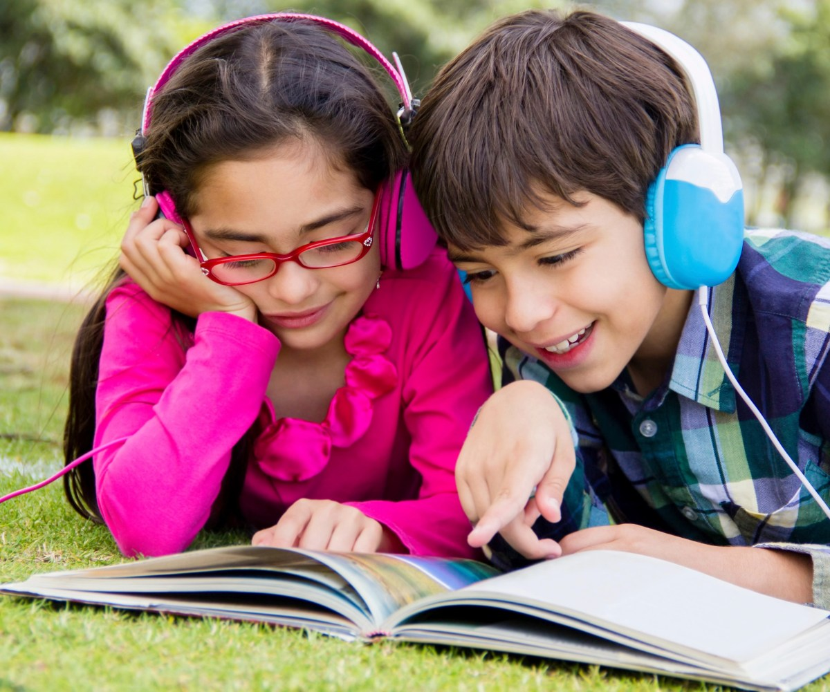 Happy kids reading at the park and listening to music