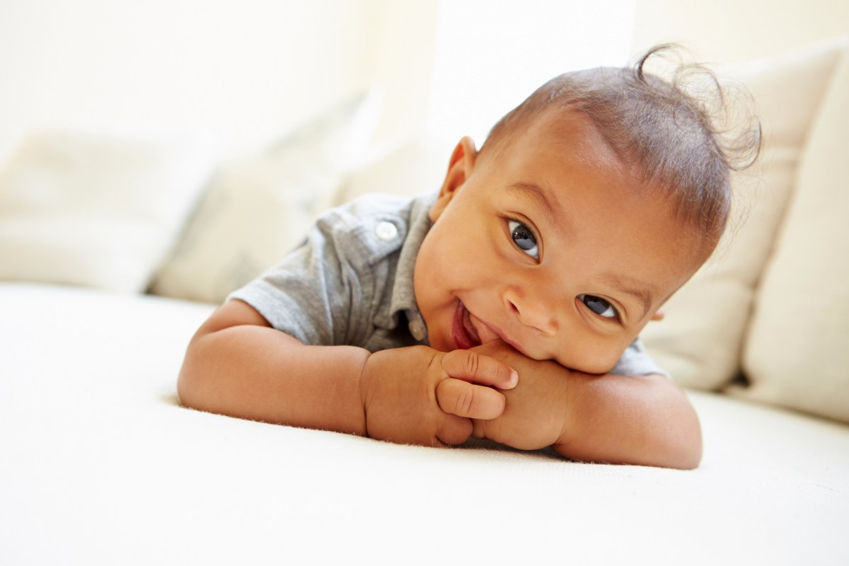 Smiling Baby Boy Lying On Tummy At Home Looking To Camera