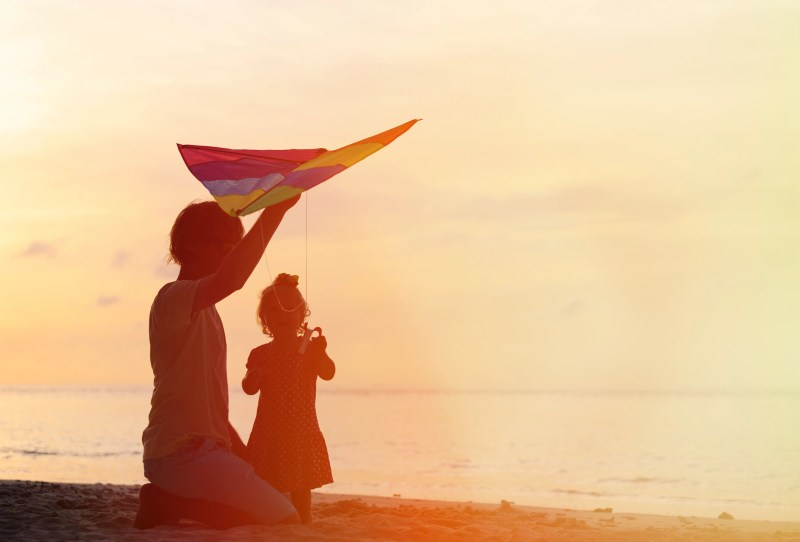 father and little daughter having fun flying kite at sunset
