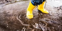 Child Wearing Yellow Rainboots Playing in Puddle after rain