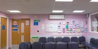 A horizontal image of an empty patient waiting room, it is typically British doctor's practice with blue chairs.