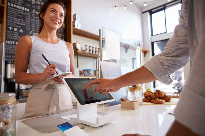 Customer using touch screen to make payment at a coffee shop