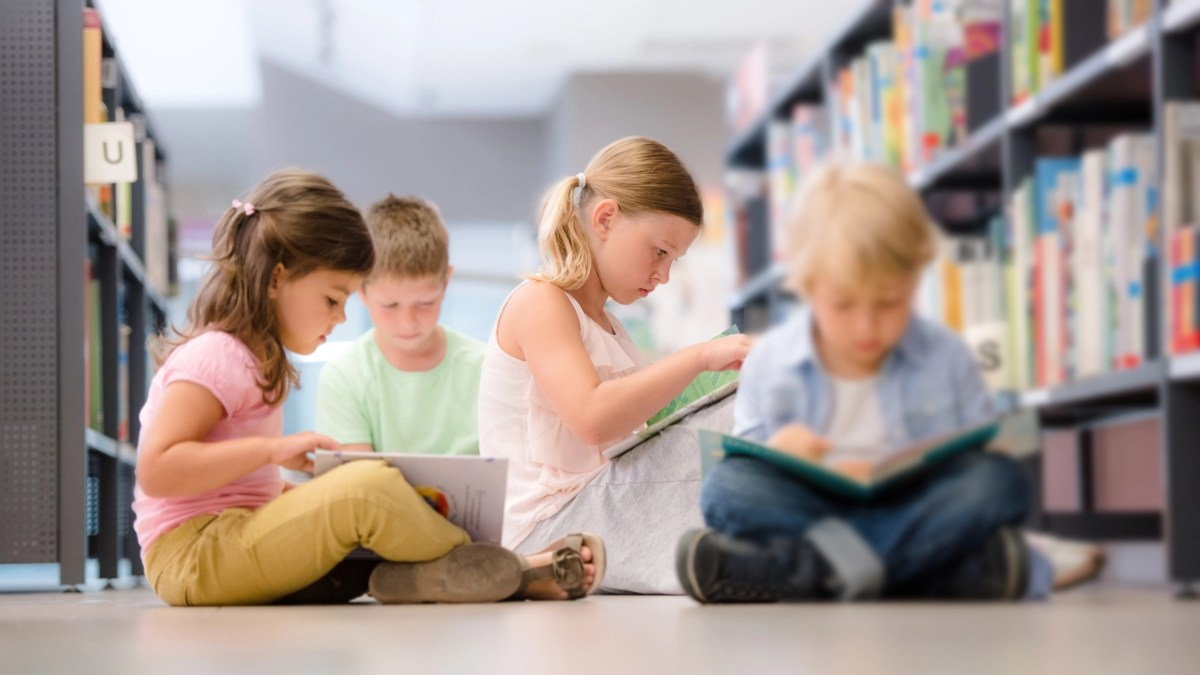 Group of children sitting on floor and reading