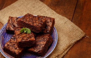 Plate with delicious chocolate brownies on dark vintage wood background.