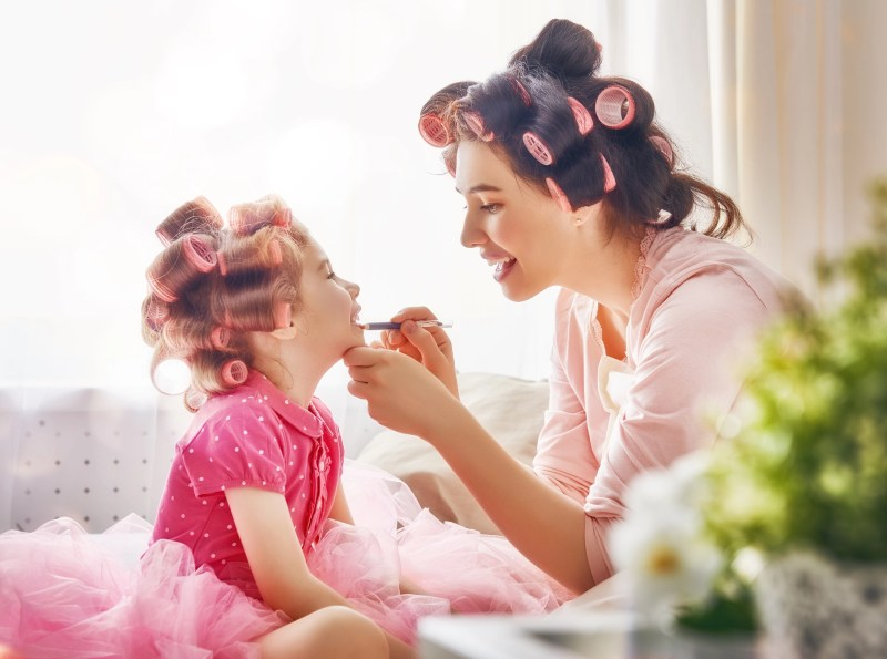 Happy loving family. Mother and daughter are doing hair and having fun. Mother putting lipstick on her daughter.