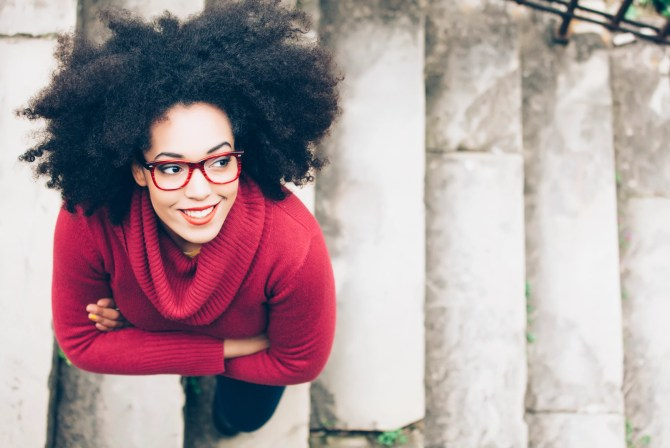 Portrait of smiling young woman standing arm crossed on staircase. High angle view. Woman with curly hair, red eyeglasses, and red pullover.