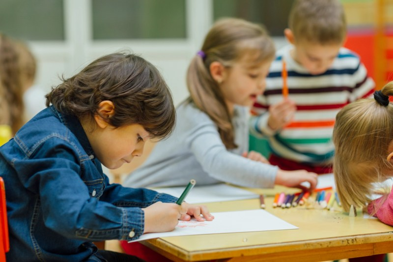 Group of children in kindergarten. Showing their imagination and skill and creativity. Focus to little boy sitting, holding pencil in his hand and drawing. Kids around are talking and drawing.