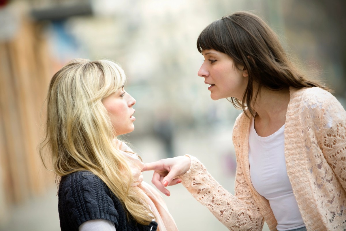 Two women talking to each other and arguing.
