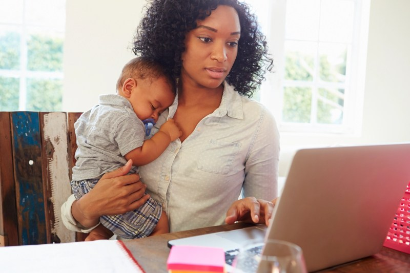 Mother With Baby Working In Office At Home Looking At Laptop