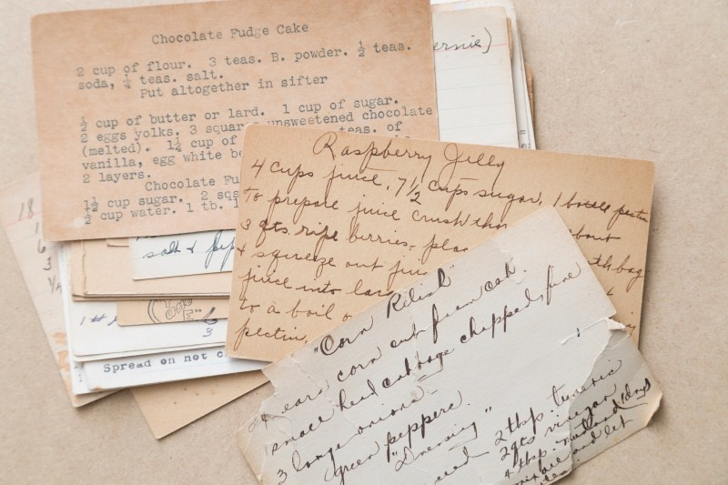 A collection of old recipe cards. Some hand written, some typed, all show signs of age. Some are more discolored than others. The recipes you can see include chocolate fudge cake, raspberry jelly, and corn relish. Studio shot.