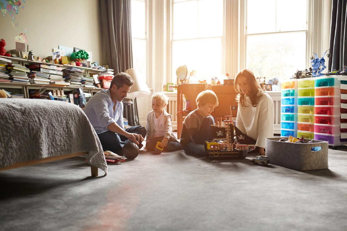 Shot of a mother and father playing with their two sons in their bedroom
