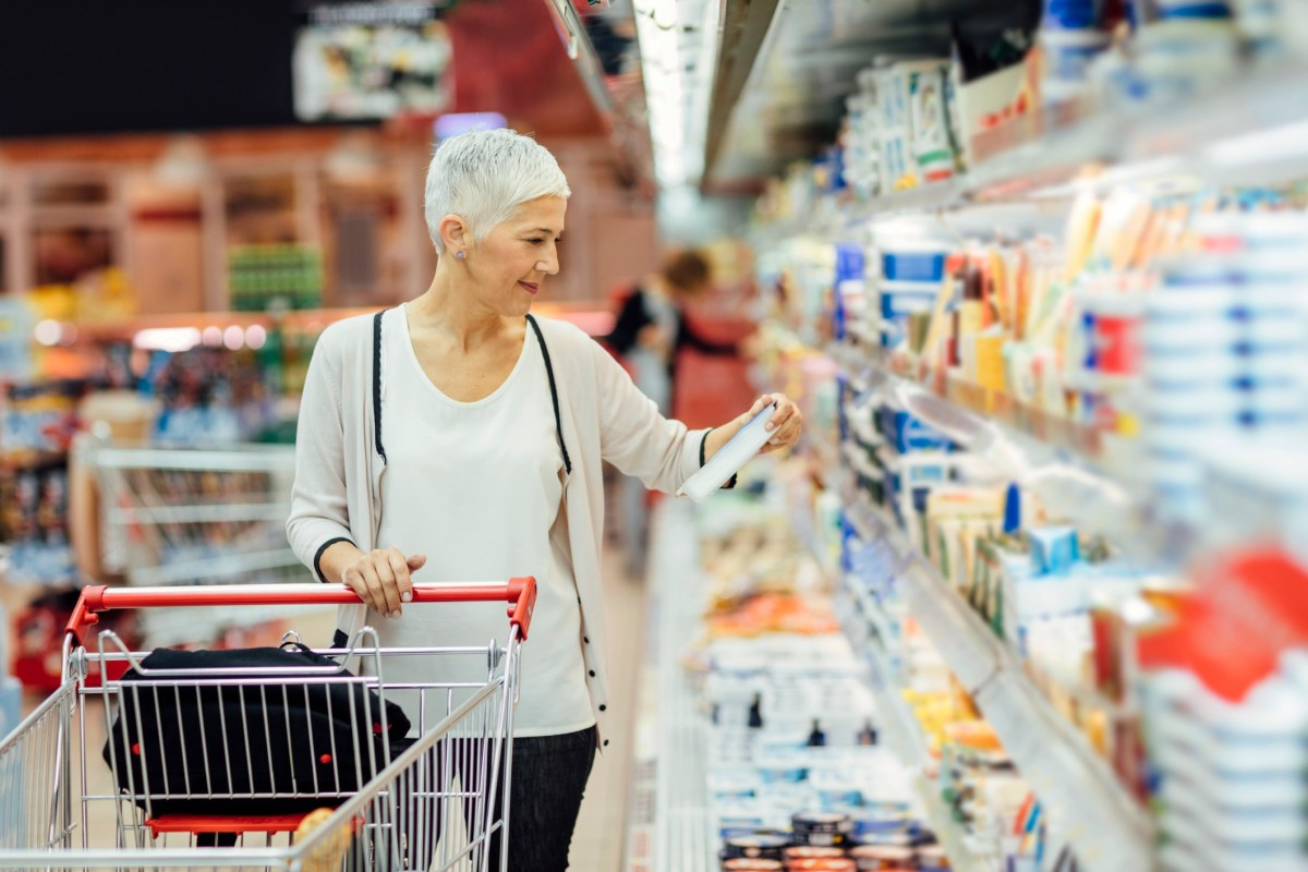 Mature smiling woman shopping in local supermarket. She is shopping groceries. Standing by produce stand and reading nutrition label on dairy product. Choosing cheese.