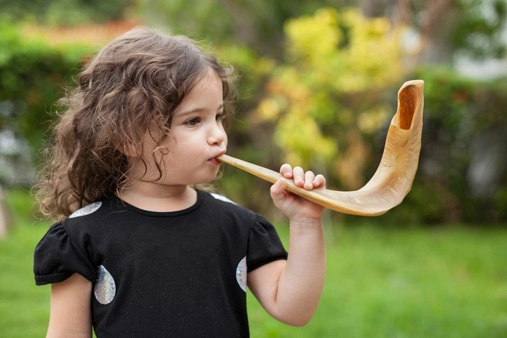 Litlte girl blowing Shofar