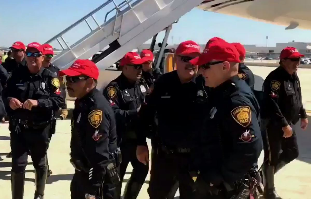 San Antonio police officers wearing Donald Trump campaign hats as the candidate leaves San Antonio. Oct. 11, 2016_360068
