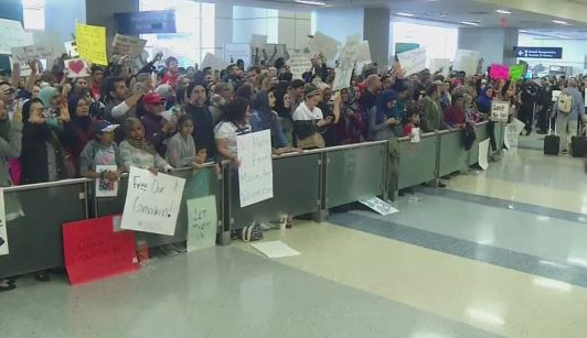 Families wait for passengers following the travel ban._431539
