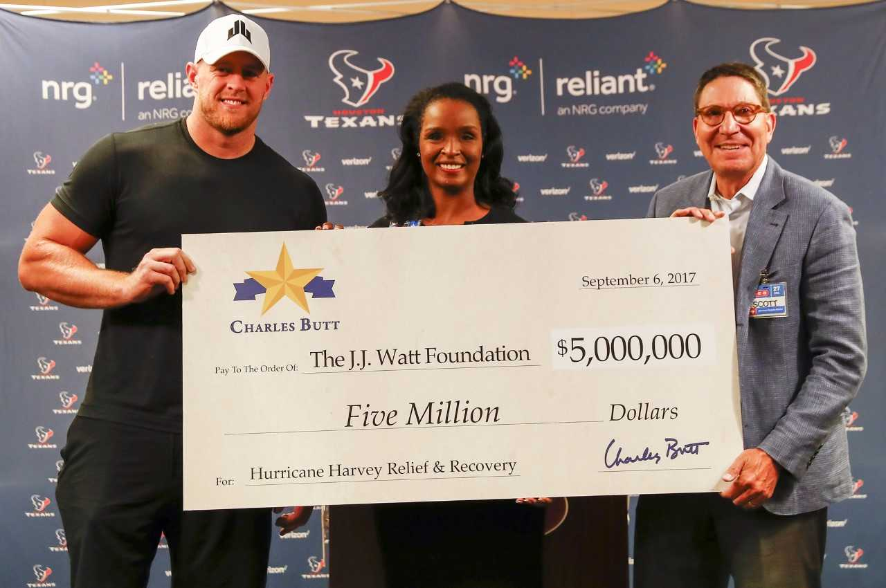 J.J. Watt, at left, receives a check for $5 million for the Harvey relief fund from Winell Herron, center, the H-E-B Group Vice President Publi_539762