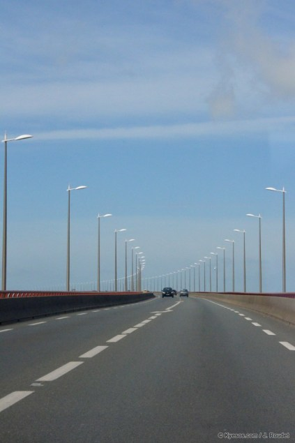 The road to now world shows a strange bridge curve with pile on empty blue sky, by Kyesos