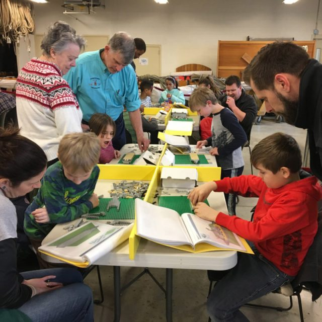 Children and parents work on LEGO shipbuilding kits that Kyle organized.