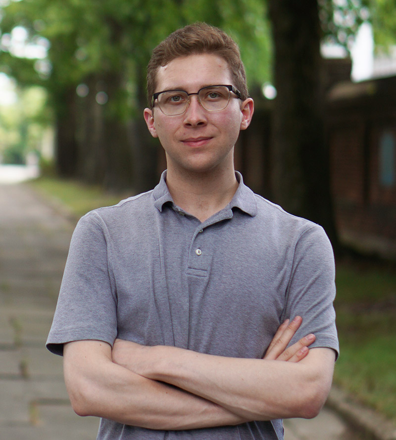 Kyle stands with his arms crossed confidently in an outdoor park and wearing professional attire.