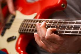 A person's hand on a guitar